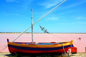 Colorful boat at pink salt lake.