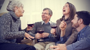Family drinking wine and laughing together.